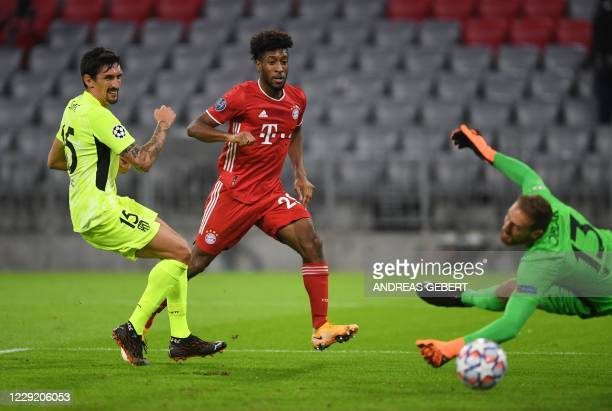 Bayern Munich's French forward Kingsley Coman scores the opening goal past Atletico Madrid's Slovenian goalkeeper Jan Oblak next to Atletico Madrid's...