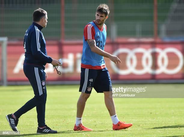 Bayern Munich's French interim coach Willy Sagnol and Bayern Munich's Spanish midfielder Javi Martinez speak together during the training session at...