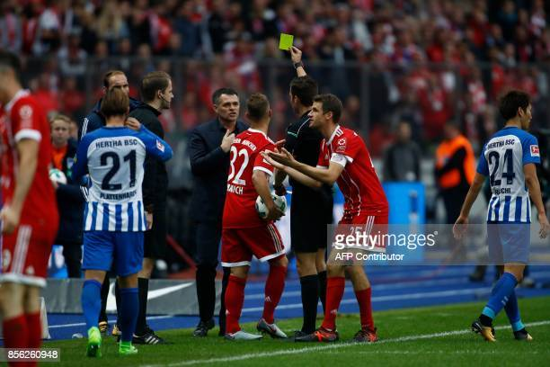 Bayern Munich's French interim head coach Willy Sagnol argues with the referee for showing Bayern Munich's German midfielder Joshua Kimmich the...