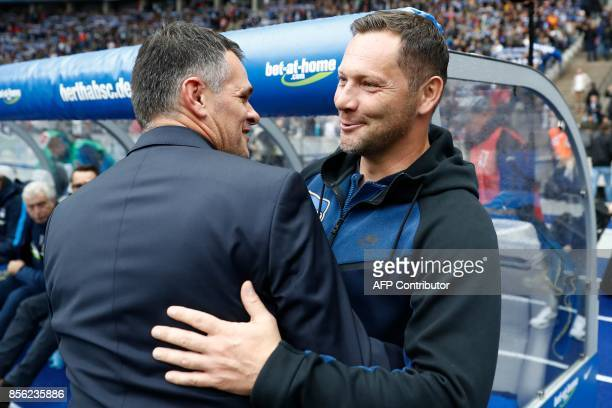 Bayern Munich's French interim head coach Willy Sagnol is greeted by Berlin's Hungarian head coach Pal Dardai as he arrives for the German first...