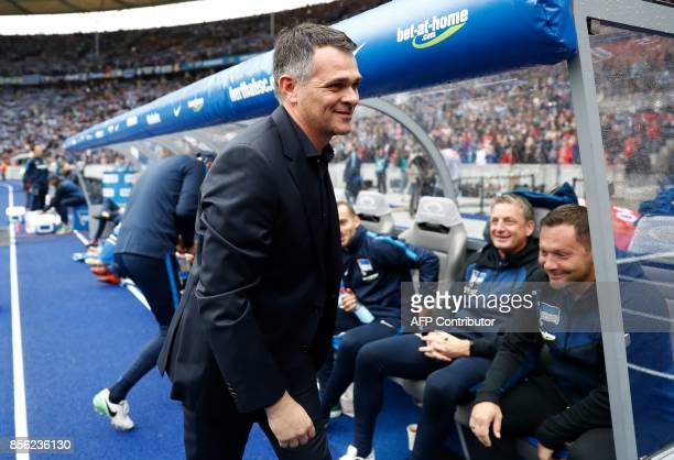 Bayern Munich's French interim head coach Willy Sagnol walks past Berlin's Hungarian head coach Pal Dardai as he arrives for the German first...