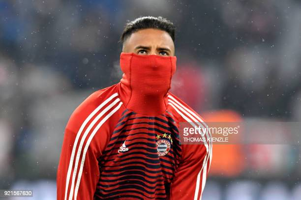 Bayern Munich's French midfielder Corentin Tolisso covers his face to protect himself from the cold during the warmup session before the UEFA...