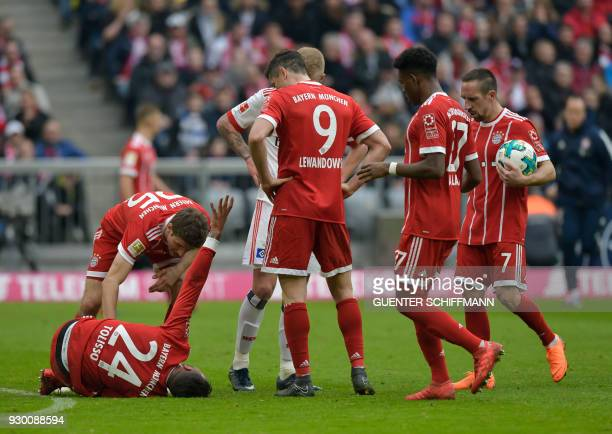 Bayern Munich's French midfielder Corentin Tolisso lies on the pitch after being injured during the German first division Bundesliga football match...