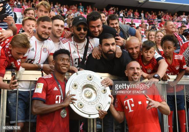 Bayern Munich's French midfielder Franck Ribery and Bayern Munich's Austrian defender David Alaba pose for a photo with fans while holding the trophy...