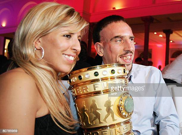 Bayern Munich's French midfielder Franck Ribery and his wife Wahiba Ribery pose with the German Cup trophy on early April 20 2008 during the Bayern...