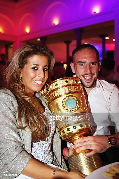 Bayern Munich's French midfielder Franck Ribery and his wife Wahiba pose with the trophy during the celebration party after the DFB German Cup final...