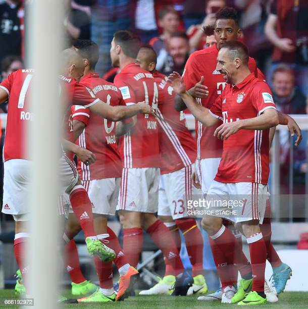 Bayern Munich's French midfielder Franck Ribery celebrates scoring the opening goal with his teammates during the German first division Bundesliga...
