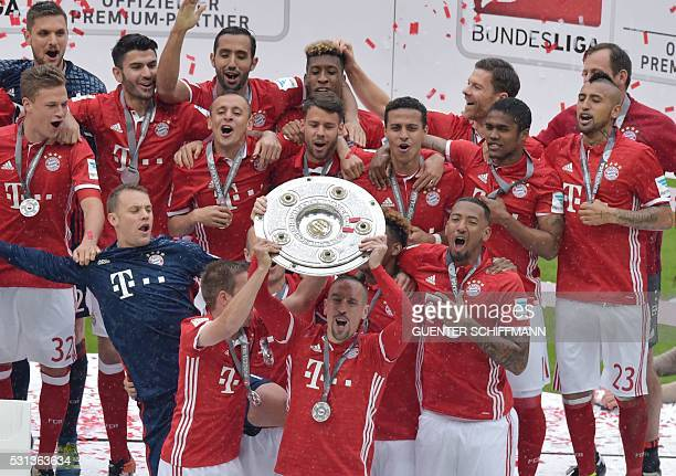 Bayern Munich's French midfielder Franck Ribery holds the Bundesliga trophy after Bayern Munich won the German title after the German first division...