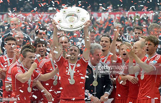 Bayern Munich's French midfielder Franck Ribery holds the German football league champion's trophy next to head coach Jupp Heynckes while celebrating...