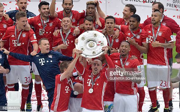 Bayern Munich's French midfielder Franck Ribery holds thetrophy aloft as he and team mates celebrate their Bundesliga title after the German first...