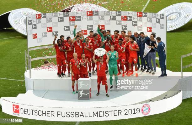 Bayern Munich's French midfielder Franck Ribery lifts the trophy as Bayern Munich's Dutch midfielder Arjen Robben Bayern Munich's Brazilian defender...