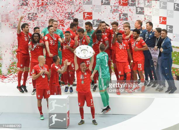 Bayern Munich's French midfielder Franck Ribery lifts the trophy as Bayern Munich's Dutch midfielder Arjen Robben Bayern Munich's Brazilian defender...