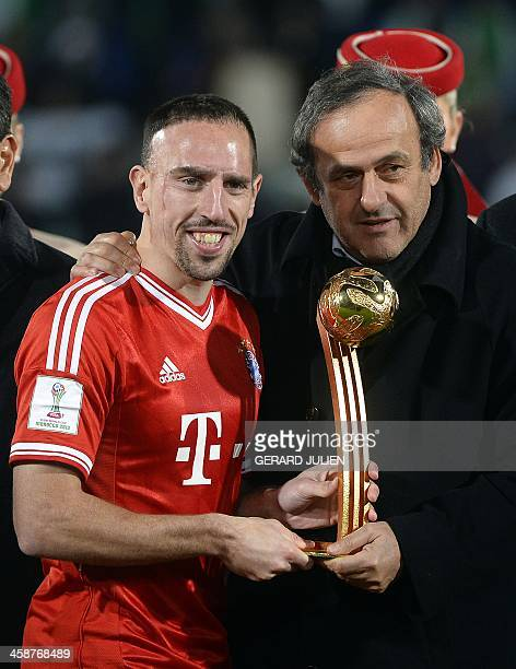 Bayern Munich's French midfielder Franck Ribery poses with UEFA president Michel Platini and the player of the tournament trophy following the 2013...