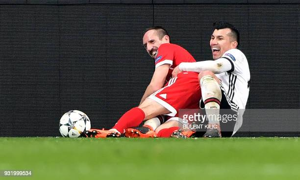 Bayern Munich's French midfielder Franck Ribery shares a light moment after a tackle with Besiktas midfielder Gary Medel during the second leg of the...