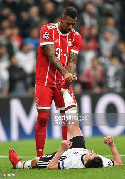 Bayern Munich's German defender Jerome Boateng helps Besiktas forward Mustafa Pektemek with cramping during the second leg of the last 16 UEFA...