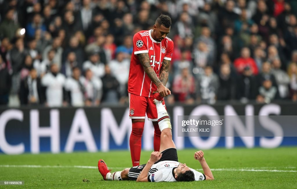 Bayern Munich's German defender Jerome Boateng (TOP) helps Besiktas forward Mustafa Pektemek with cramping during the second leg of the last 16 UEFA Champions League football match between Besiktas and Bayern Munich at Besiktas Park in Istanbul on March 14, 2018. / AFP PHOTO / Bulent Kilic