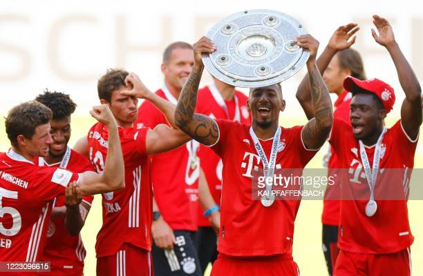 Bayern Munich's German defender Jerome Boateng lifts the trophy as Bayern Munich players celebrate after the German first division Bundesliga...