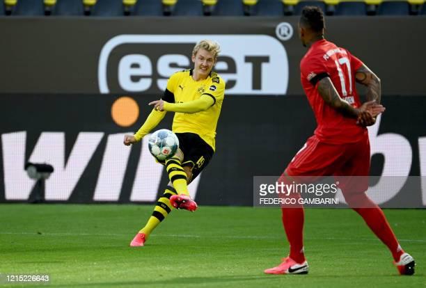 Bayern Munich's German defender Jerome Boateng reacts as Dortmund's German forward Julian Brandt kicks the ball during the German first division...