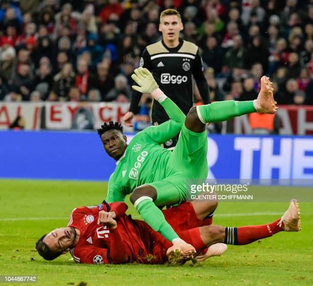 Bayern Munich's German defender Mats Hummels and Ajax's Cameroon goalkeeper Andre Onana vie for the ball during the UEFA Champions League Group E...