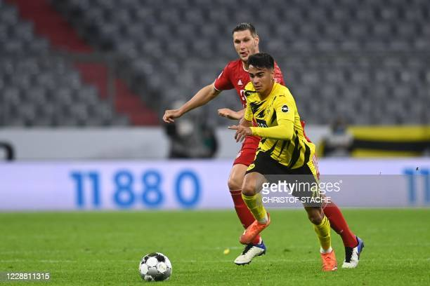 Bayern Munich's German defender Niklas Suele and Dortmund's Brazilian midfielder Reinier vie for the ball during the German Supercup football match...