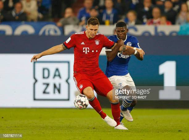 Bayern Munich's German defender Niklas Suele and Schalke's Swiss forward Breel Embolo vie with the ball during the German First division Bundesliga...