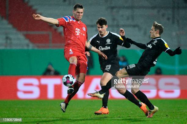 Bayern Munich's German defender Niklas Suele vies for the ball with Holstein Kiel's German forward Janni Luca Serra and Holstein Kiel's German...