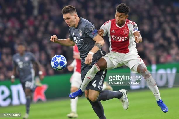 Bayern Munich's German defender Niklas Suele vies with Ajax's Brazilian forward David Neres during the UEFA Champions League Group E football match...