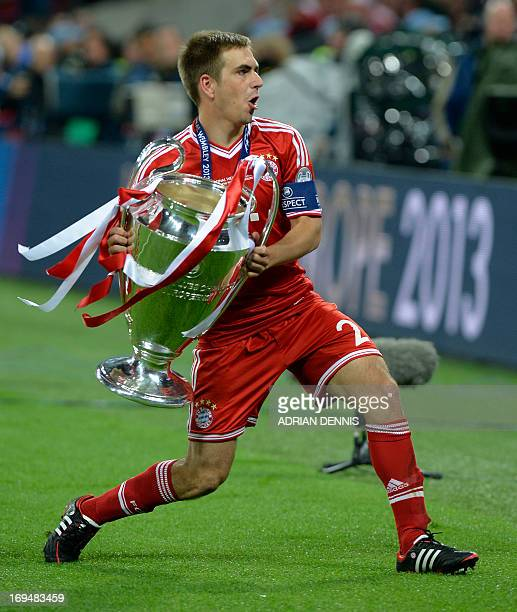 Bayern Munich's German defender Philipp Lahm celebrates with the trophy on the pitch after their victory in the UEFA Champions League final football...