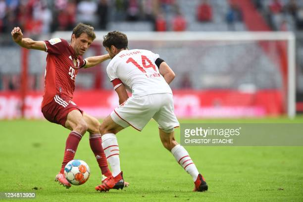 Bayern Munich's German forward Thomas Mueller and Cologne's German defender Jonas Hector vie for the ball during the German first division Bundesliga...