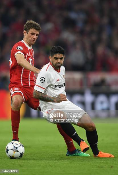 Bayern Munich's German forward Thomas Mueller and Sevilla's Argentinian midfielder Ever Banega vie for the ball during the UEFA Champions League...
