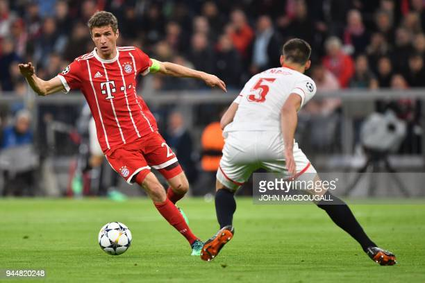 Bayern Munich's German forward Thomas Mueller and Sevilla's French defender Clement Lenglet vie for the ball during the UEFA Champions League...