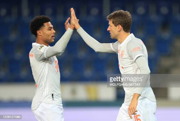 Bayern Munich's German forward Thomas Mueller celebrates scoring the 01 goal with Bayern Munich's German midfielder Serge Gnabry during the German...