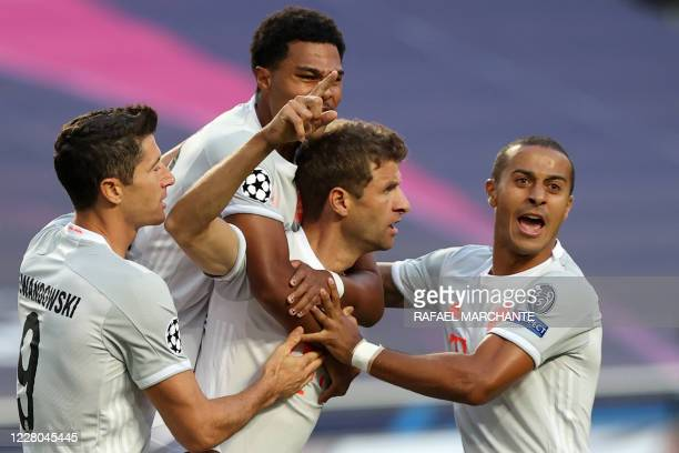 Bayern Munich's German forward Thomas Mueller celebrates with teammates after scoring a goal during the UEFA Champions League quarterfinal football...