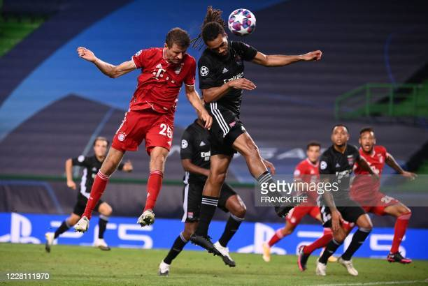 Bayern Munich's German forward Thomas Mueller heads the ball with Lyon's Belgian defender Jason Denayer during the UEFA Champions League semi-final...