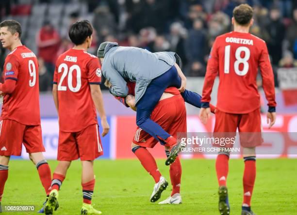 Bayern Munich's German forward Thomas Mueller jumps on Bayern Munich's German defender Niklas Suele after the UEFA Champions League Group E football...