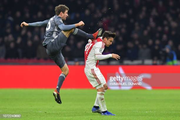 Bayern Munich's German forward Thomas Mueller kicks the back of Ajax's Aregntine defender Nicolas Tagliafico during the UEFA Champions League Group E...