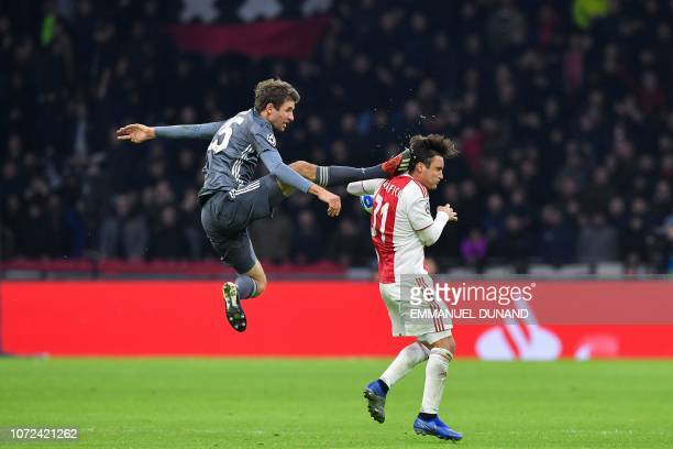 TOPSHOT Bayern Munich's German forward Thomas Mueller kicks the back of Ajax's Argentine defender Nicolas Tagliafico during the UEFA Champions League...