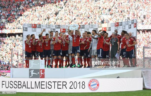 Bayern Munich's German forward Thomas Mueller lifts the trophy during the celebration for the 28th German football championship after the German...