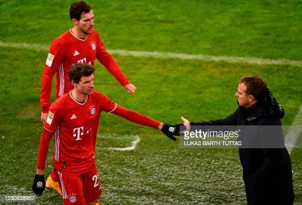 Bayern Munich's German forward Thomas Mueller shake hands with Bayern Munich's German head coach Hans-Dieter Flick during the German first division...