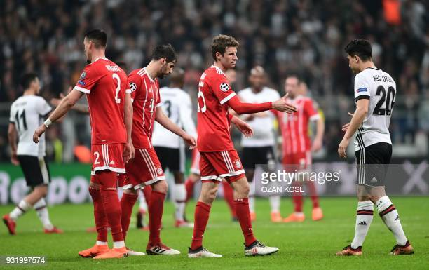 Bayern Munich's German forward Thomas Mueller shakes hands with Besiktas midfielder Necip Uysal after the second leg of the last 16 UEFA Champions...