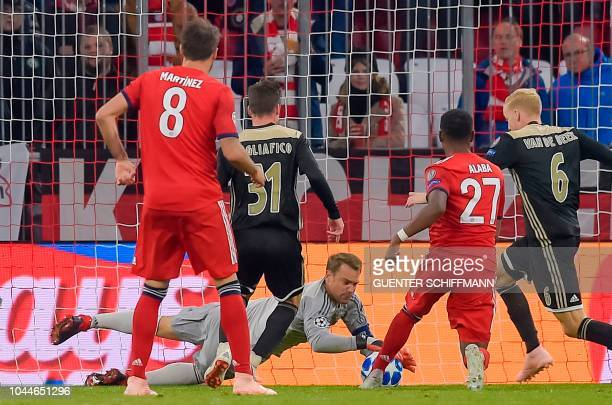 Bayern Munich's German goal keeper Manuel Neuer and Ajax Amsterdam's Argentian defender Nicolas Tagliafico vie for the ballvie for the ball during...