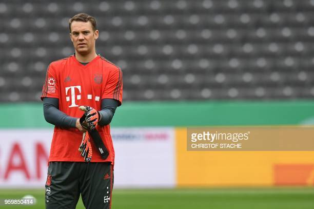 Bayern Munich's German goalkeeper Manuel Neuer adjusts his gloves prior a training session of Bayern Munich's German football team on May 18 at the...