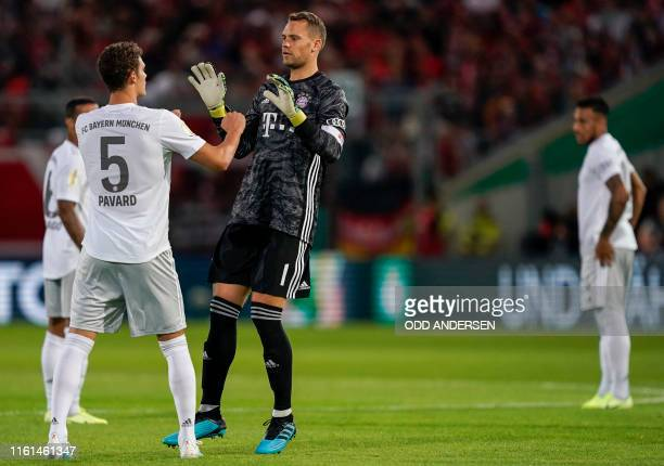 Bayern Munich's German goalkeeper Manuel Neuer and Bayern Munich's French defender Benjamin Pavard speak during the German Cup first round football...
