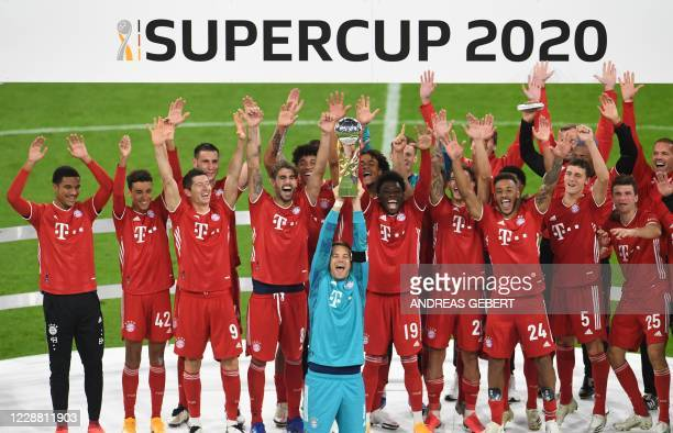 Bayern Munich's German goalkeeper Manuel Neuer and teammates celebrate with the trophy after winning the German Supercup football match FC Bayern...