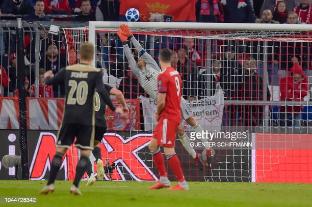 Bayern Munich's German goalkeeper Manuel Neuer dives for the ball during the UEFA Champions League Group E football match between Bayern Munich and...