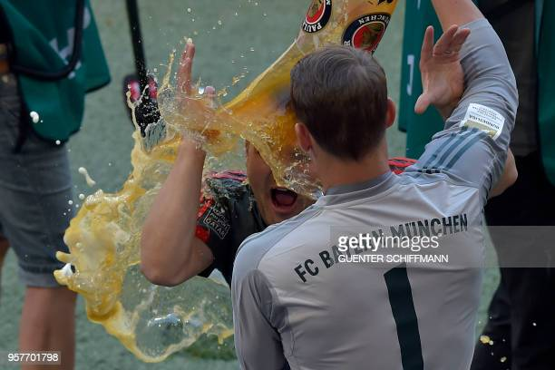 Bayern Munich's German goalkeeper Manuel Neuer douses a teammate with beer as they celebrate their victory at the end of the German first division...