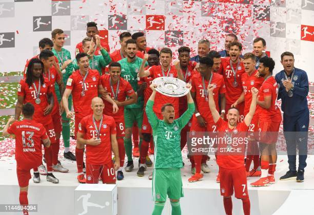 Bayern Munich's German goalkeeper Manuel Neuer lifts the trophy as Bayern Munich players including Bayern Munich's French midfielder Franck Ribery...