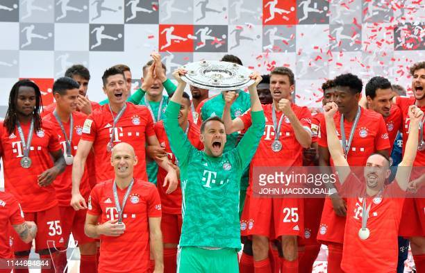 Bayern Munich's German goalkeeper Manuel Neuer lifts the trophy as Bayern Munich players celebrate after the German First division Bundesliga...