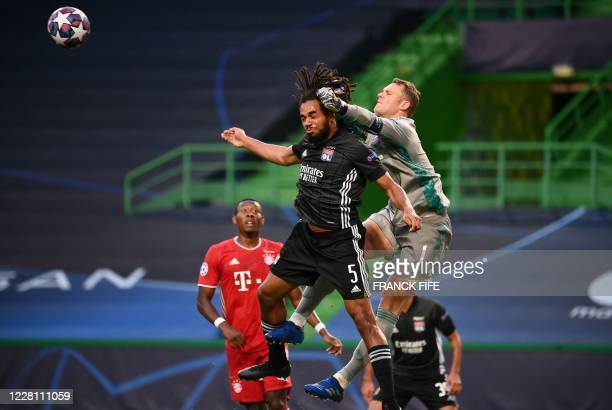 Bayern Munich's German goalkeeper Manuel Neuer punches the ball away as Lyon's Belgian defender Jason Denayer jumps for a header during the UEFA...