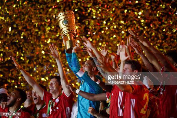 Bayern Munich's German goalkeeper Manuel Neuer raises the German Cup trophy as he and his teammates celebrate winning the final football match Bayer...